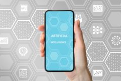 AI / artificial intelligence concept. Hand holding modern frameless smartphone in front of neutral background with icons Royalty Free Stock Photos