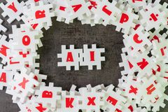 AI, Artificial Intelligence with deep learning or machine learning concept, white puzzle jigsaw building the word AI on dark black stock image