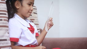 Aian liten flicka i minnestavlan för thailändsk student för dagis den enhetliga användande klara glass för futursistic cybertekno stock video