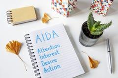 AIDA Attention Interest Desire Action som är skriftlig i en anteckningsbok royaltyfri foto