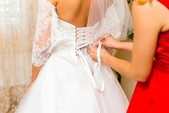 Aidant la jeune mariée à s'habiller dans la robe de mariage Photos stock