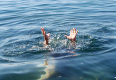 Aide. Bâton de mains hors de l'eau image stock