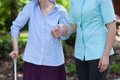 Aide d'infirmière handicapée avec la marche Image stock