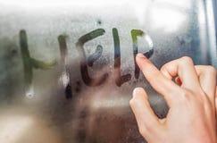 Aide d'inscription d'écriture d'enfant sur le verre humide Photos libres de droits