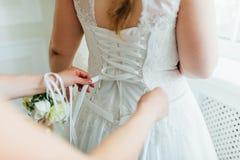 Aide de demoiselles d'honneur pour porter une robe de mariage Photo libre de droits