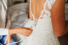Aide de demoiselles d'honneur pour porter une robe de mariage Photos stock