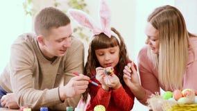 Aide de père et de mère la fille de décorer l'oeuf de pâques banque de vidéos