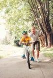 Aide de père sa petite bicyclette de tour de fils photo stock