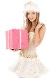 Aide de Santa dans le corset et la jupe avec le cadeau rose Image stock