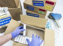 Aide humanitaire, infirmière plaçant des boîtes avec le médicament pour envoyer le Venezuela photographie stock libre de droits