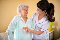 Aide la vieille femme supérieure à marcher avec l'aide des béquilles Photographie stock