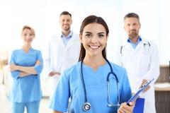 Aide médical avec des collègues dans la clinique photos stock