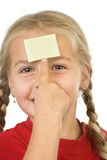 Aide memoir. A little girl points on a sticky note (place for your own text)  on her forehead Royalty Free Stock Photo