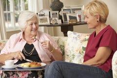 Aide servant la femme supérieure avec le repas dans la maison de soin photos stock