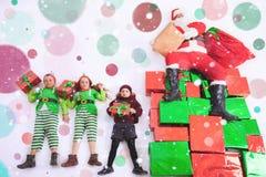 Aides du ` s de Santa fonctionnant au Pôle Nord Il liste de souhaits de lecture Images stock