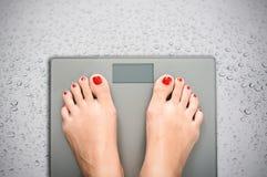 Aidez à perdre des kilogrammes avec des pieds de femme faisant un pas sur une échelle de poids Photographie stock
