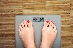 Aidez à perdre des kilogrammes avec des pieds de femme faisant un pas sur une échelle de poids Images stock