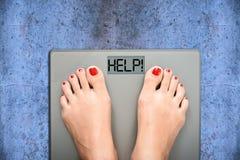 Aidez à perdre des kilogrammes avec des pieds de femme faisant un pas sur une échelle de poids Image libre de droits