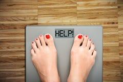 Aidez à perdre des kilogrammes avec des pieds de femme faisant un pas sur une échelle de poids Photo stock