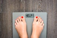 Aidez à perdre des kilogrammes avec des pieds de femme faisant un pas sur une échelle de poids Images libres de droits