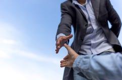 Aidez la main de concept atteignant pour aider quelqu'un avec le ciel bleu Image stock