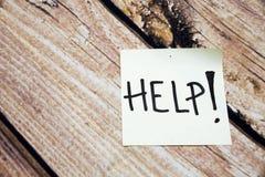 Aidez le papier de note jaune de bâton sur le fond en bois images stock