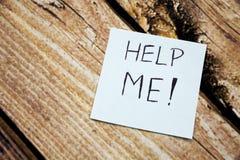 Aidez-moi écrit sur une note collante sur le fond en bois Images stock