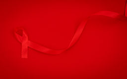 Aids Awareness Red heart Ribbon on red background . Stock Photos