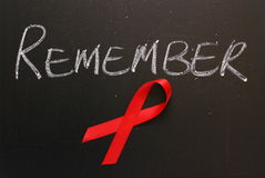 Aids Awareness Remember. Red Aids awareness ribbon on a blackboard under the word Remember Royalty Free Stock Image