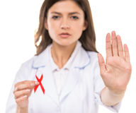 AIDS. Beautiful female doctor holding red ribbon as a symbol of AIDS royalty free stock photo