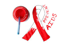 Aids ribbon. Pot of red paint and paintbrush.  Unfinished stock photos