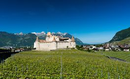 Aigle, VD / Switzerland - 31 May 2019: the historic castle at Aigle in the Swiss canton of Vaud with summer vineyards. The historic castle at Aigle in the Swiss royalty free stock photography