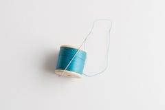 Aiguille attachée dessus à la bobine du fil bleu Photos stock
