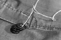 Aiguille avec le fil et les boutons, jeans Photos stock