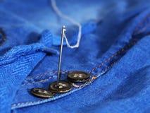 Aiguille avec le fil et les boutons, jeans Image libre de droits