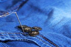 Aiguille avec le fil et les boutons, jeans Image stock