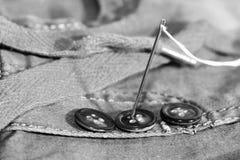 Aiguille avec le fil et les boutons, jeans Photos libres de droits