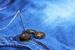 Aiguille avec le fil et les boutons, jeans Images libres de droits