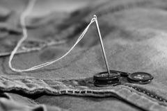 Aiguille avec le fil et les boutons, jeans Photo libre de droits