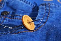 Aiguille avec le fil et les boutons, jeans Images stock