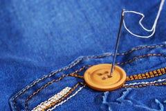 Aiguille avec le fil et les boutons, jeans Photo stock