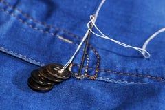 Aiguille avec le fil et les boutons, jeans Photographie stock libre de droits