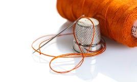 Aiguille avec un fil orange et un dé Photos libres de droits
