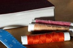 Aiguille, bobines avec des fils, livre et un ruban métrique Photos stock