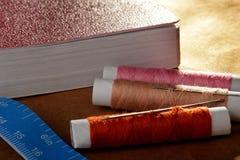Aiguille, bobines avec des fils, livre et un ruban métrique Image libre de droits
