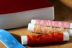 Aiguille, bobines avec des fils, livre et un ruban métrique Photos libres de droits