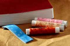 Aiguille, bobines avec des fils, livre et un ruban métrique Images libres de droits