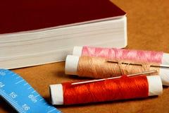 Aiguille, bobines avec des fils, livre et un ruban métrique Photo stock