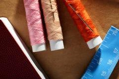 Aiguille, bobines avec des fils, livre et un ruban métrique Photographie stock libre de droits