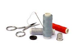 Aiguille, dé, ciseaux, fil et bouton Photographie stock